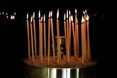 Wax candles in an orthodox church. Burning yellow easter  candles  in an orthodox church in greek Royalty Free Stock Image