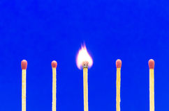 Burnning match setting on blue background for ideas and inspirat Royalty Free Stock Photo