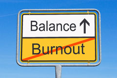 Burnout and balance sign. Conceptual sign with burnout crossed out and directional arrowing pointing to balance, blue sky background Royalty Free Stock Photo