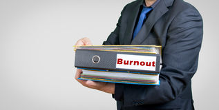 Burnout businessman. A businessman with folders an burnout text Royalty Free Stock Photo