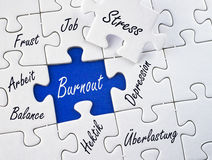 Burnout jigsaw. A conceptual picture of a jigsaw puzzle and different related words. German text: burnout, stress, job, frustration, work, balance, depression Royalty Free Stock Photos