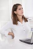 Burnout: müde junge Geschäftsfrau, die zurück die Stirn runzelt und ausdehnt Stockbild