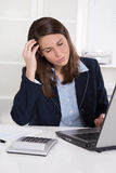 Burnout: overworked tired businesswoman in blue scratching head. At desk with laptop and calculator - to much work Royalty Free Stock Photography