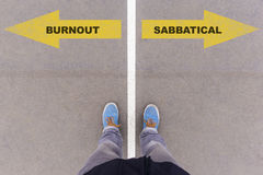 Burnout or sabbatical text on asphalt ground, feet and shoes on Stock Image