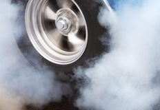 Burnout with spinning wheel. A car doing a burnout so that the tires spin smoke and smell of rubber Royalty Free Stock Image