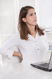 Burnout: tired young businesswoman frowning and stretching back Stock Image