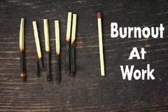 Burnout At Work. Burnt matches on the wooden table and text Burnout At Work stock images