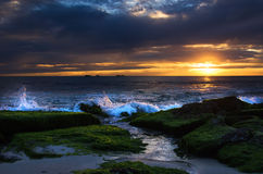 Burns Beach Sunset. Splashing waves on to the shore at Burns beach on a beautiful summer sunset Stock Image