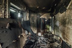 Burnt apartment house interior. Burned furniture and charred walls in black soot Stock Photography