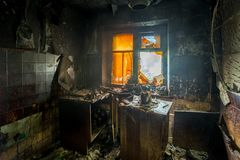Burnt apartment house interior. Burned furniture and charred walls in black soot Royalty Free Stock Images