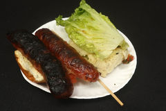 Burnt bbq sausage link with lettuce, bun, paper plate and toothpick. BBQ chorizo sandwich on a roll with lettuce, and toothpick on a disposable plate Royalty Free Stock Photos