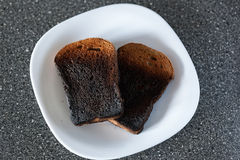Burnt bread from the toaster on a plate. Bad cooking Royalty Free Stock Photos
