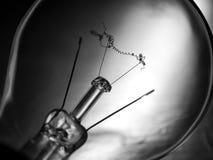 Burnt bulb. Light bulb with a burnt coil on a dark background Stock Photos