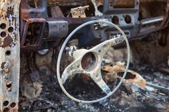 Burnt car interior with steering wheel after the accident Stock Image