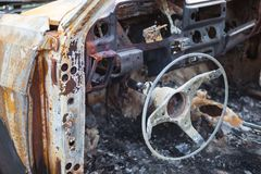 Burnt car interior with steering wheel after the accident Stock Photography
