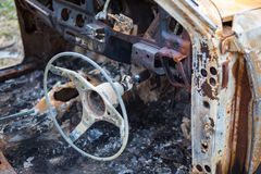 Burnt car interior with steering wheel after the accident Royalty Free Stock Photos
