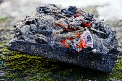 Heat with ash and coals on an iron scoop on a green moss. Burnt coal with a fervor of ash on an iron old shovel Royalty Free Stock Photos