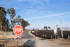 Burnt Farm Field with Railway Crossing in Foreground Royalty Free Stock Images