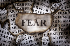 Burnt Fear. Burnt pieces of paper with the word Fear. Close-up stock photography