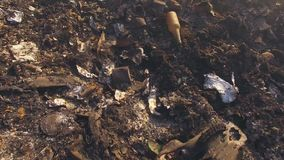 Burnt Garbage On Huge Dump Site. AERIAL VIEW. Lots of burnt garbage producing smoke lying on the ground on huge dump site among withered grass stock video footage
