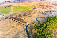 Burnt grass in field, aerial landscape. Narrow river flowing along small forest. Burnt grass in field, aerial landscape. Narrow river flowing along a small stock photos