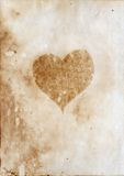 Burnt heart. Silhouette on the aged paper Royalty Free Stock Photography