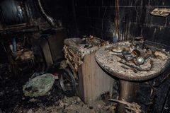 Burnt house interior. Burned burnt bathroom, Fused remains of furniture and washing machine.  royalty free stock photography