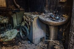 Burnt house interior. Burned burnt bathroom, Fused remains of furniture and washing machine.  stock images