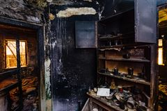 Burnt house interior. Burned furniture, kitchen cabinet, charred walls and ceiling in black soot.  stock photos
