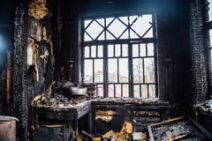 Burnt house interior. Burned kitchen, remains of furniture in black soot.  stock photography