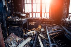 Burnt house interior. Burned kitchen, remains of furniture in black soot.  stock image