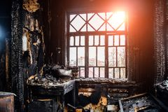 Burnt house interior. Burned kitchen, remains of furniture in black soot.  royalty free stock images