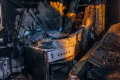 Burnt house interior. Burned kitchen, remains of stove and furniture in black soot.  royalty free stock photos