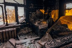 Burnt house interior. Burned kitchen, remains of stove and furniture in black soot.  stock image