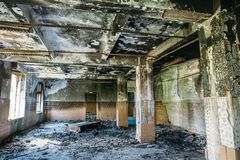 Burnt house interior. Burned room with columns, charred walls and ceiling in black soot. Toned stock photo