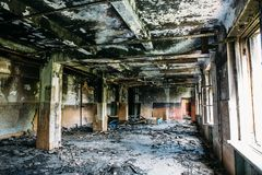 Burnt house interior. Burned room with columns, charred walls and ceiling in black soot. Toned royalty free stock image