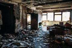 Burnt house interior. Burned room in industrial building, charred furniture and damaged apartment after fire. Toned royalty free stock image