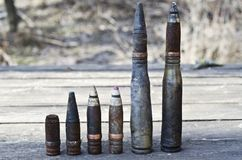 Burnt large-caliber shells and bullets with and without sleeves, affected by the explosion near on a wooden table Stock Image