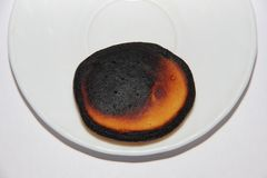 Burnt little pancake lies on the edge of a white plate, which is located on a white background Stock Photo