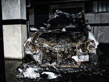 Burnt Out Car in an Underground Garage. After an electrical fire with water puddle Royalty Free Stock Images