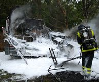 Burnt out caravan. Fire in caravan extinguished by firefighter Royalty Free Stock Photo