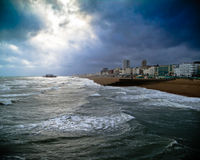 A burnt out pier off the cost of Brighton. A burned out pier off the coast of Brighton sea side under dark clouds on a windy day Stock Images