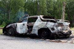 Burnt out rusted old car near the road and forest Royalty Free Stock Photo