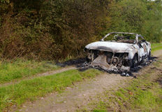 Burnt out Saab car on farm track Royalty Free Stock Image