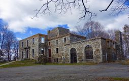 Burnt out shell of stone mansion destroyed by fire. Ominous framework of old burnt down stone mansion in winter with bare tree branches all around it, menacing Royalty Free Stock Photo