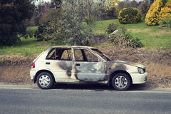 Burnt out stolen car abandonded on the roadside Royalty Free Stock Photos