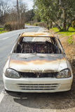 Burnt out stolen car abandonded on the roadside Royalty Free Stock Images