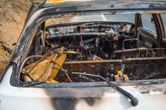 Burnt out stolen car abandonded on the roadside, the rear window Stock Photos
