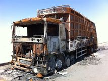 Burnt out truck in desert. A desert road through Oman with a burnt out truck Royalty Free Stock Photos