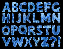 Burnt paper alphabet  on white background. Vintage decrepit cyan ink color cardboard latin typescript with dark indigo spots on black backdrop with clipping path Stock Photos